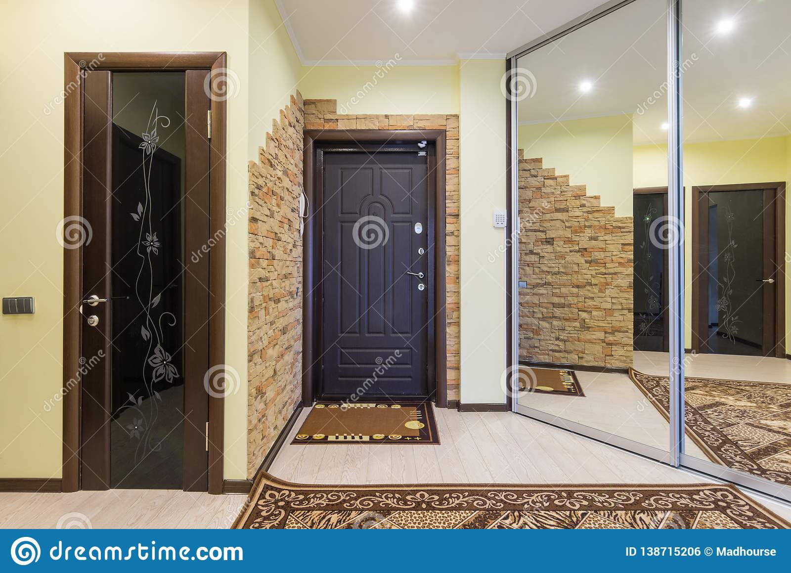 Spacious entrance hall in the apartment with built-in wardrobe and mirrors