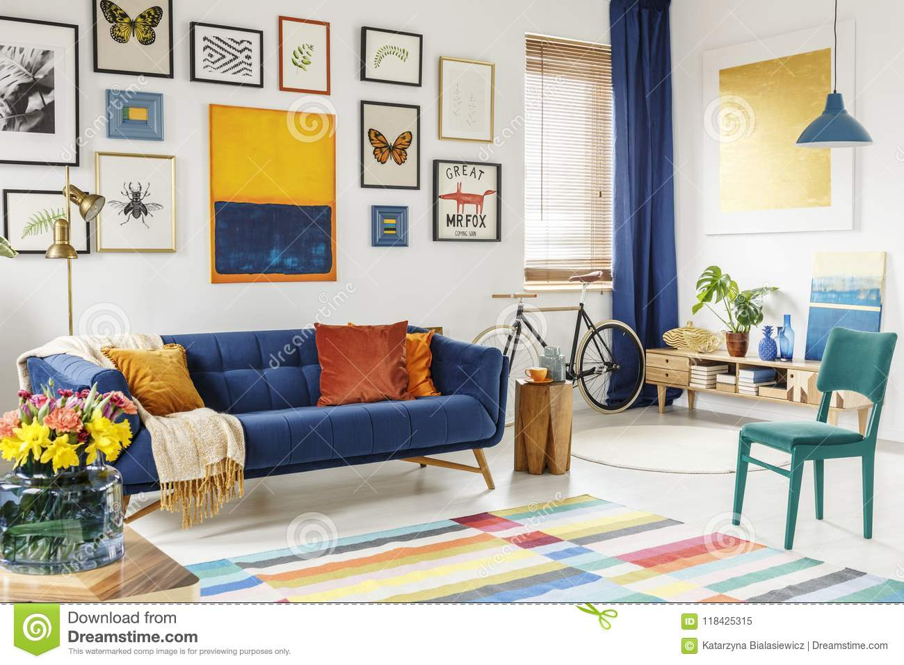 Spacious living room interior with a blanket and orange pillows on a blue sofa green chair colorful rug and gallery of posters and painting on white wall
