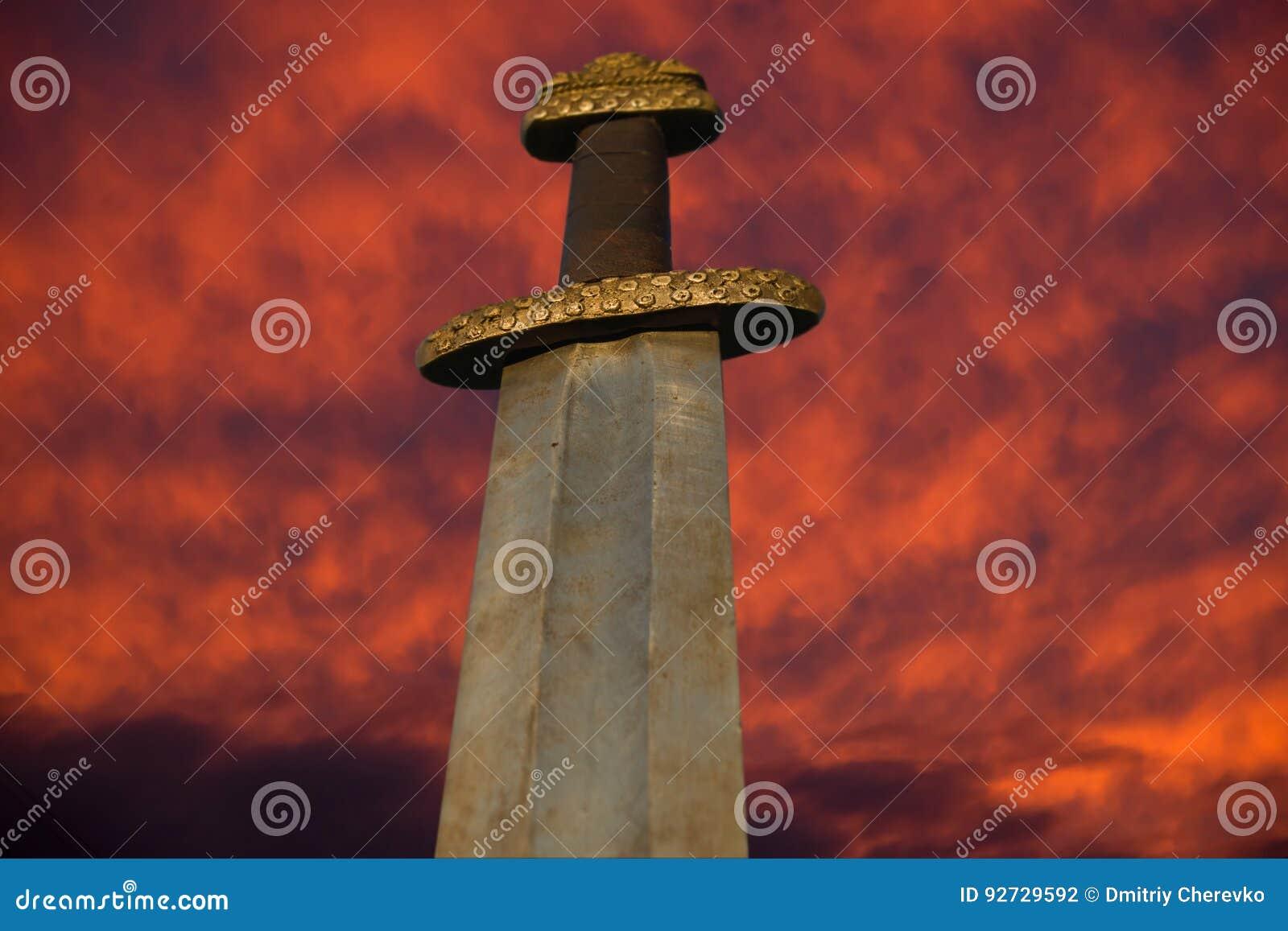 Spada medievale di vichingo contro un cielo drammatico
