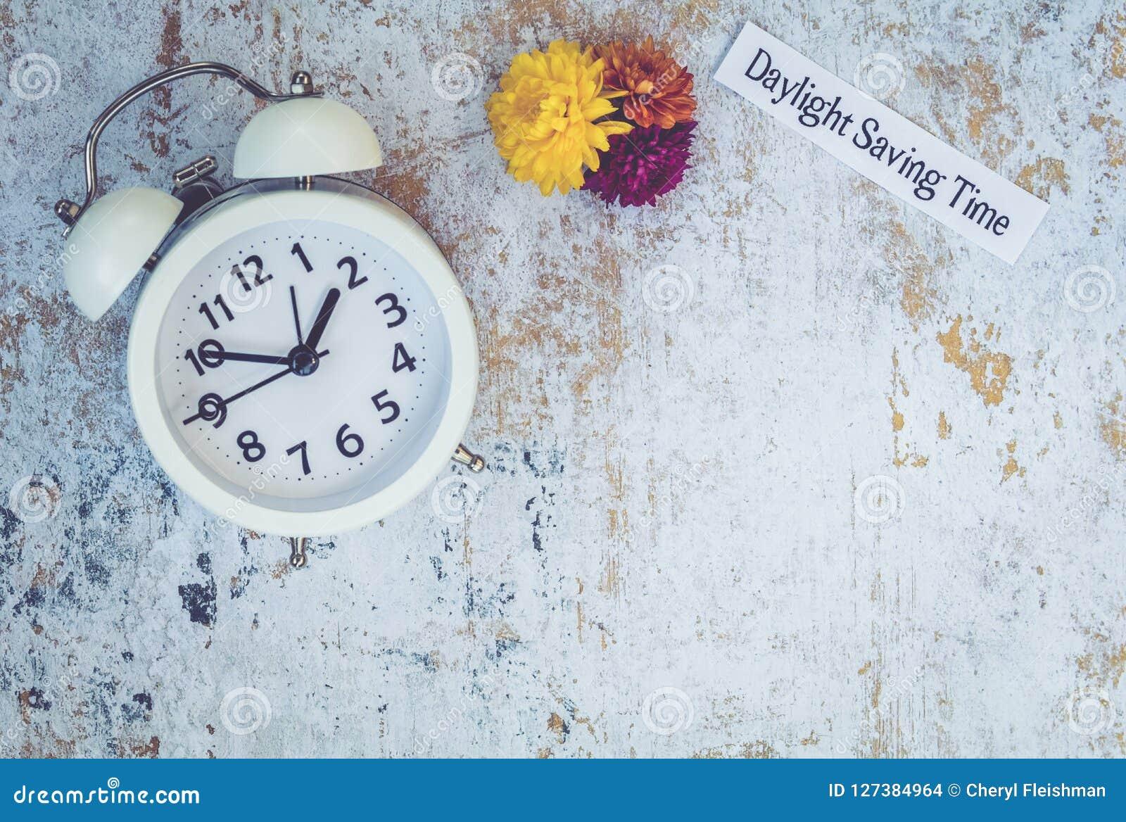 Spadku światła dziennego oszczędzania czasu pojęcie z bielu zegarem i kwiatami, mieszkanie nieatutowy