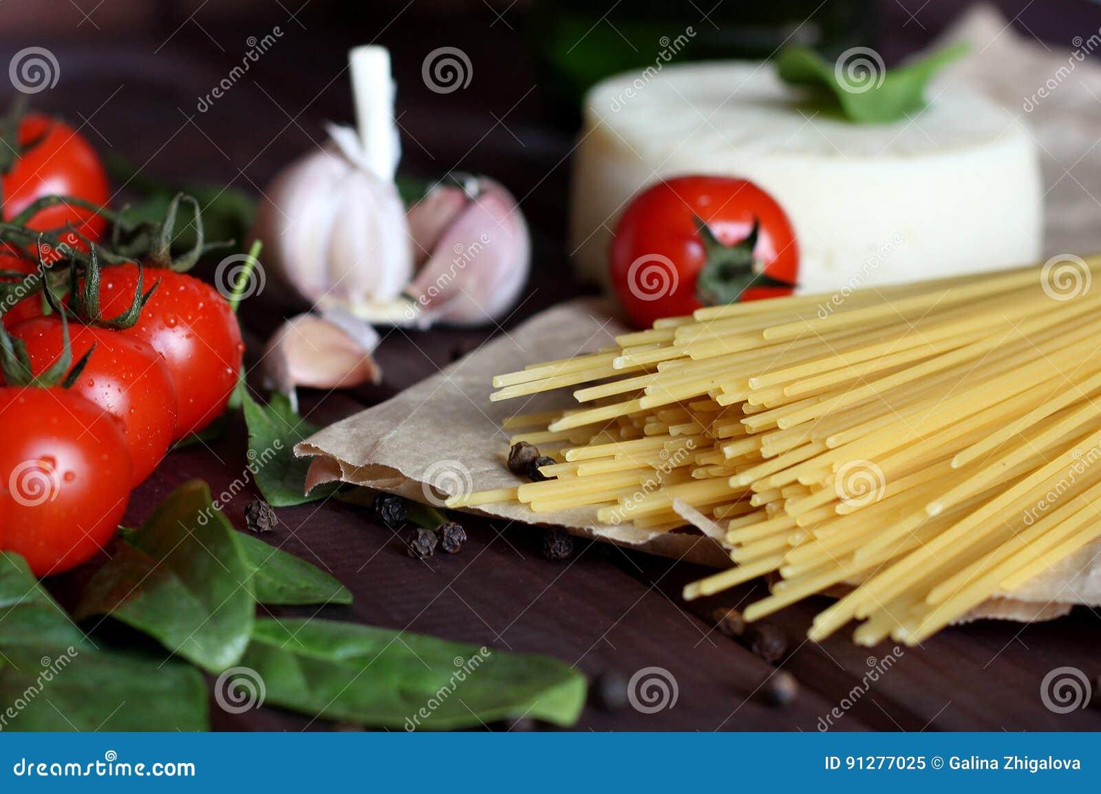 Spagetti körsbärsröda tomater, ost, vitlök, spenat, peppar på mörk wood bakgrund