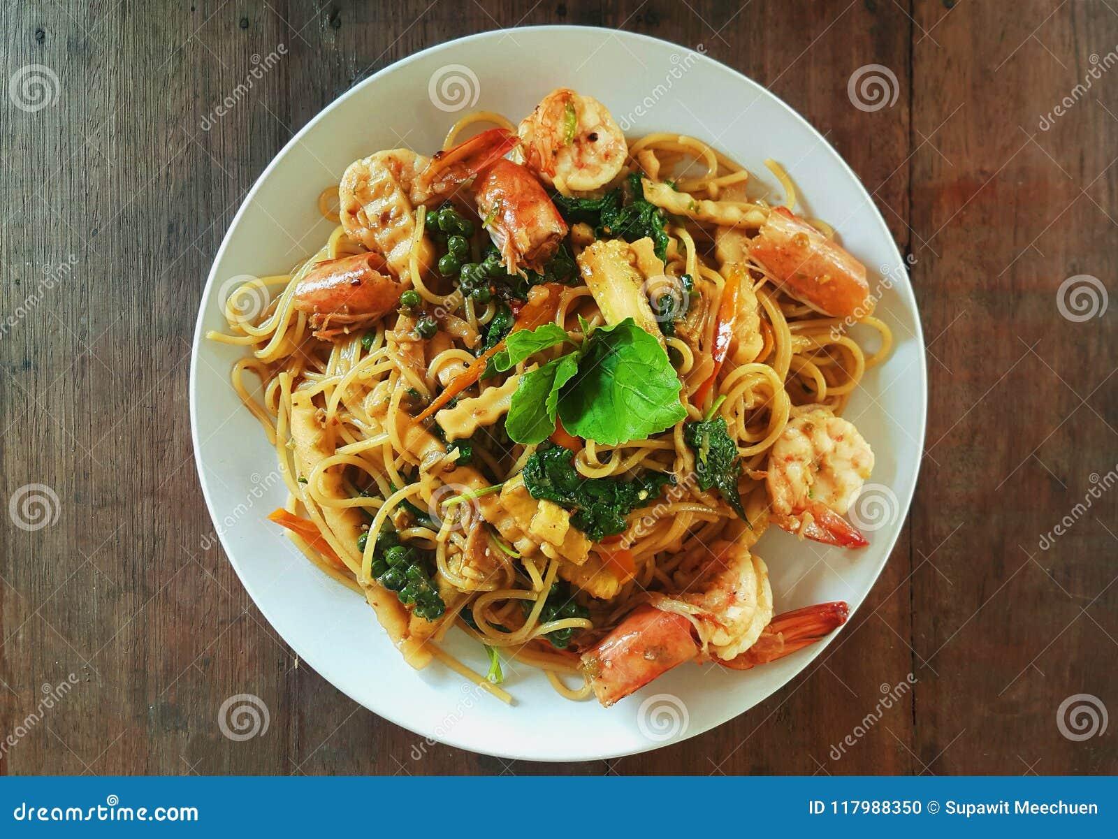 Spagettiuppståndelse stekte den kryddiga thai blockkien mao med räka på trätabellen
