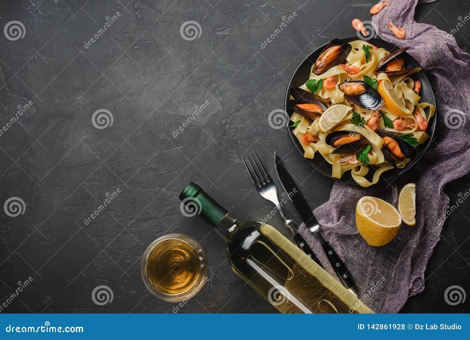 Spagettivongole, italiensk havs- pasta med musslor och musslor, i platta med örter och exponeringsglas av vitt vin på den lantlig