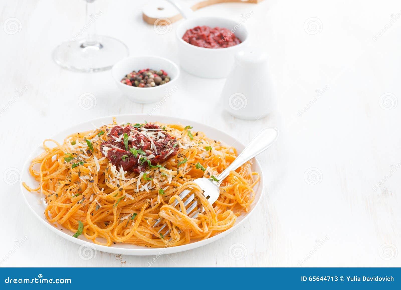Spaghetti avec la sauce tomate et le parmesan sur la table en bois blanche