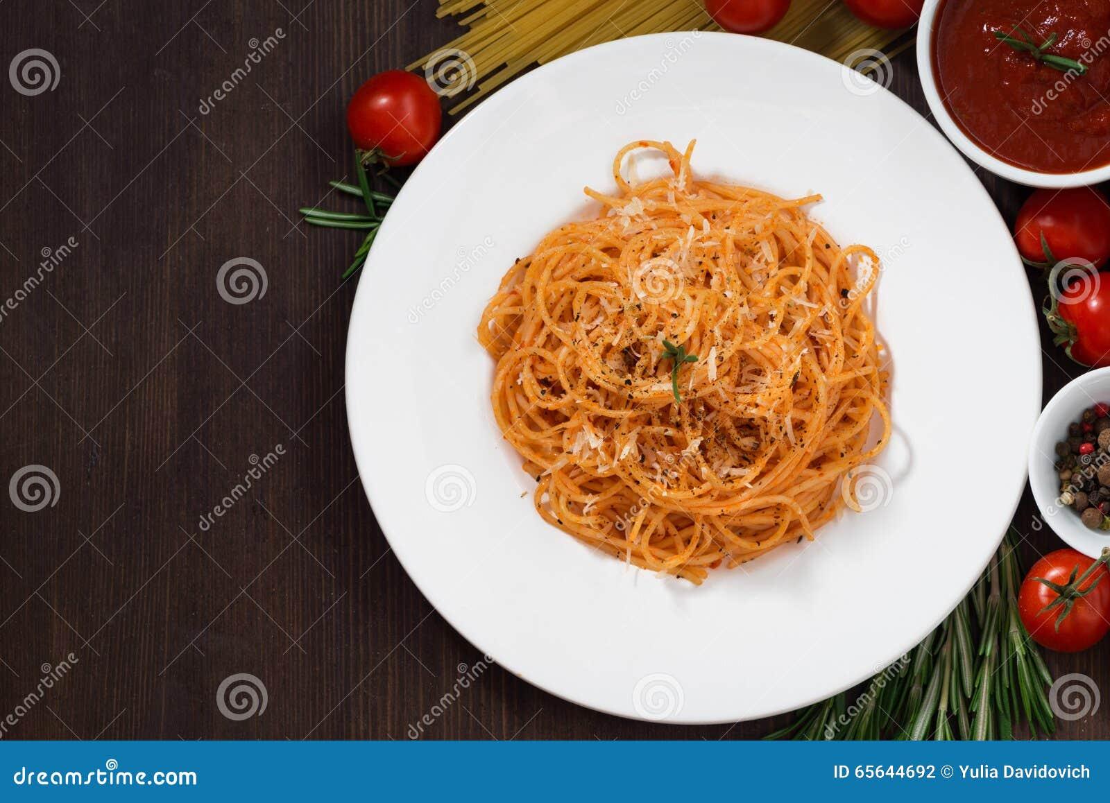 Spaghetti avec la sauce tomate et les ingrédients sur une table en bois