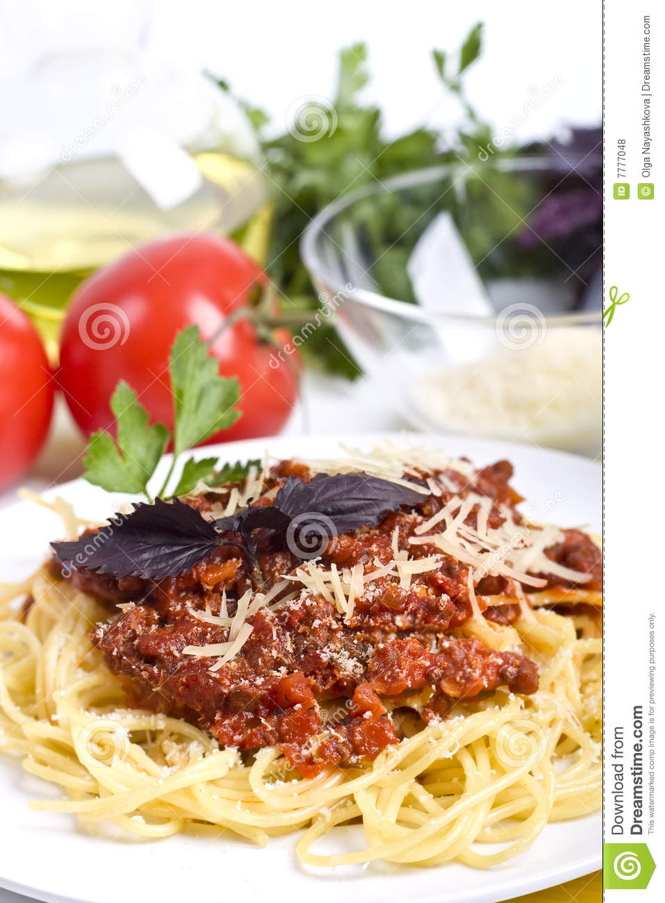 Spaghetti bolognese servwd on a white plate with basil and grated