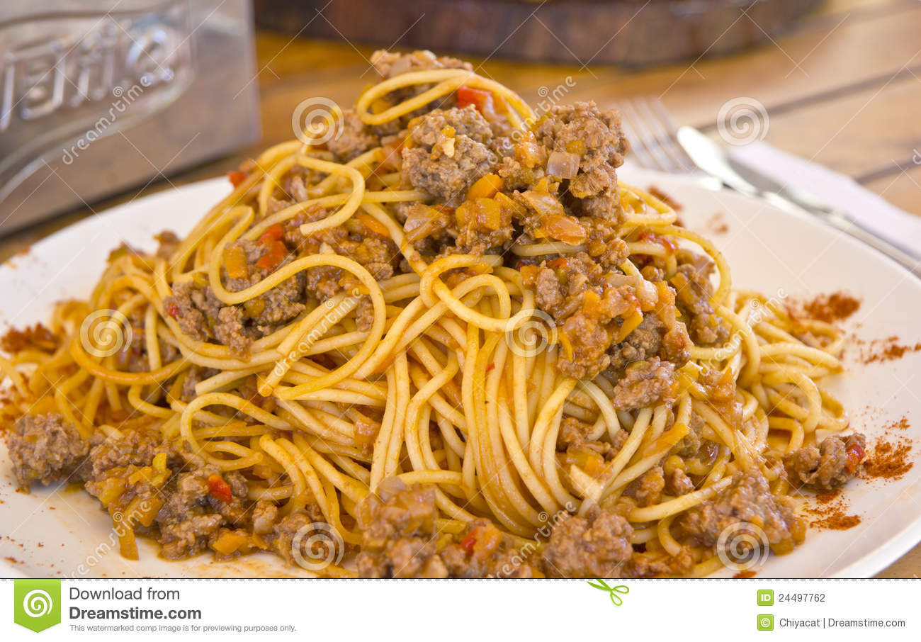 Plateful of spaghetti with Bolognese sauce in an outdoor restaurant.