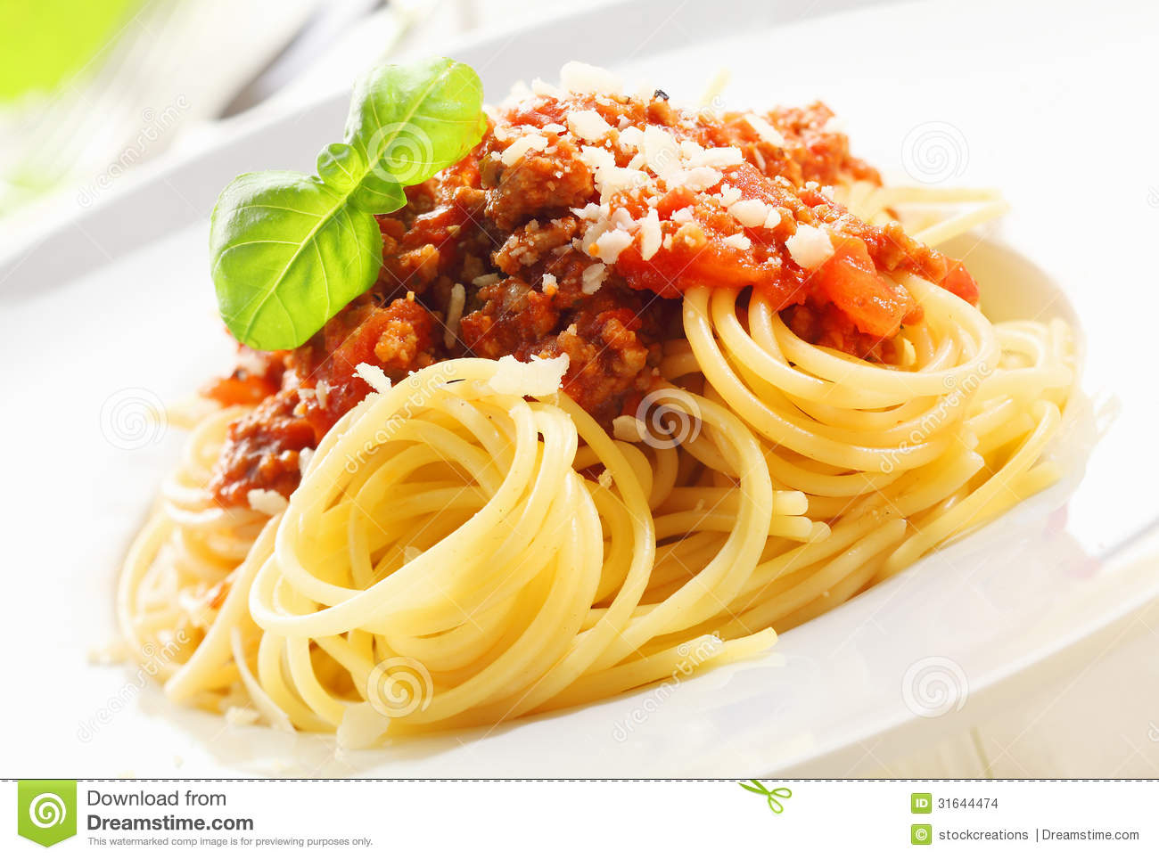 Closeup of coiled cooked Italian spaghetti topped with Bolognese sauce ...