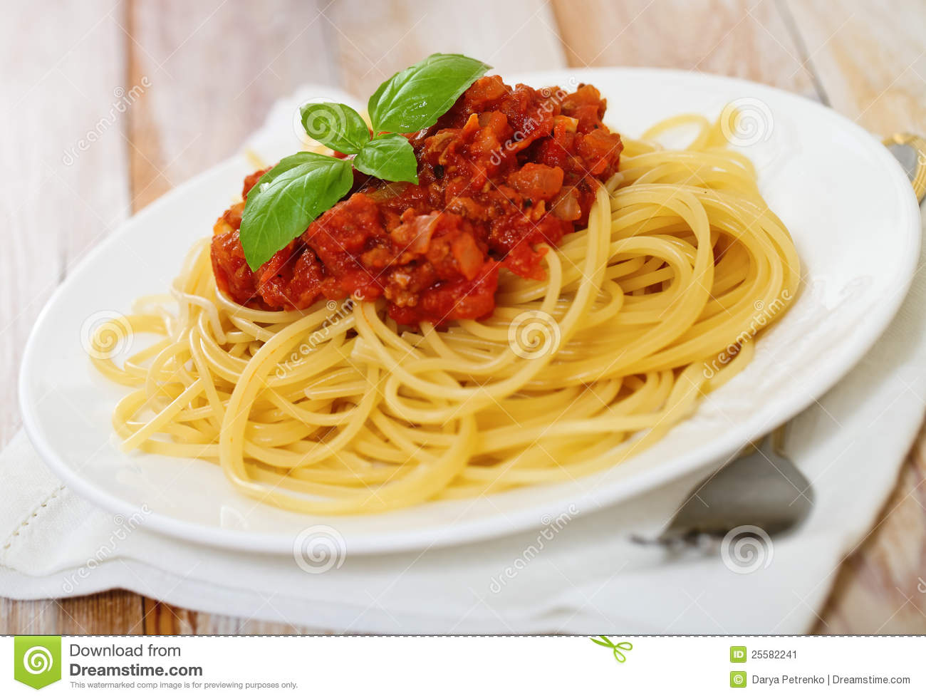 Spaghetti bolognese on white plate on wooden table