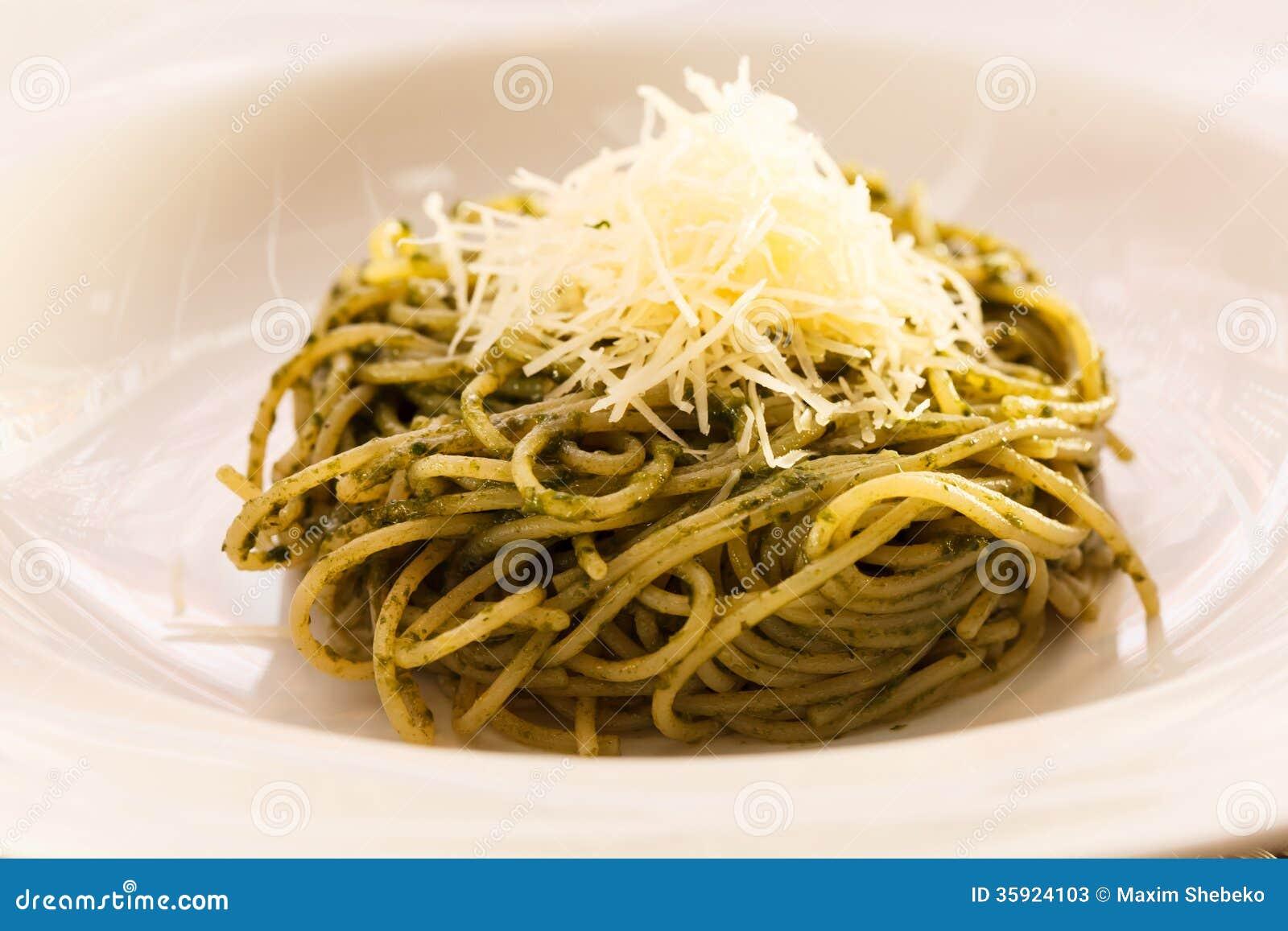 Spaghetti die met pesto wordt gemengd