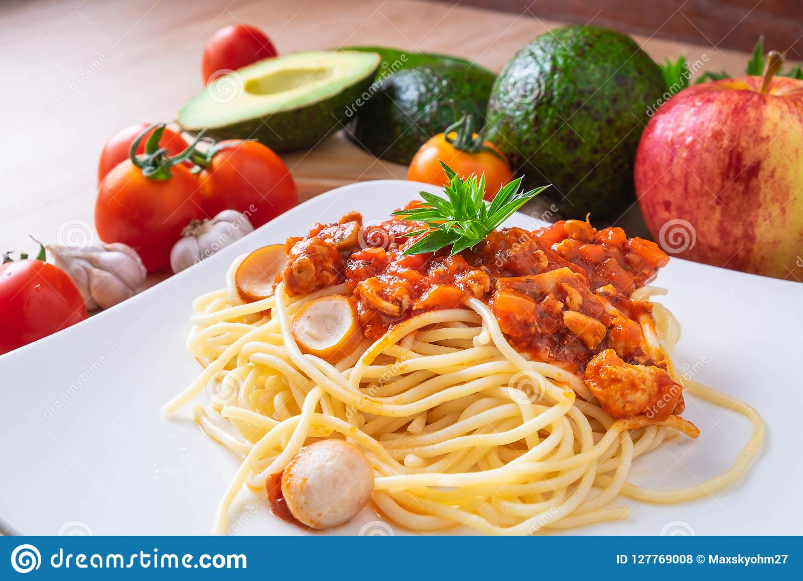 Spaghetti en verse tomaten met kruiden op houten raad