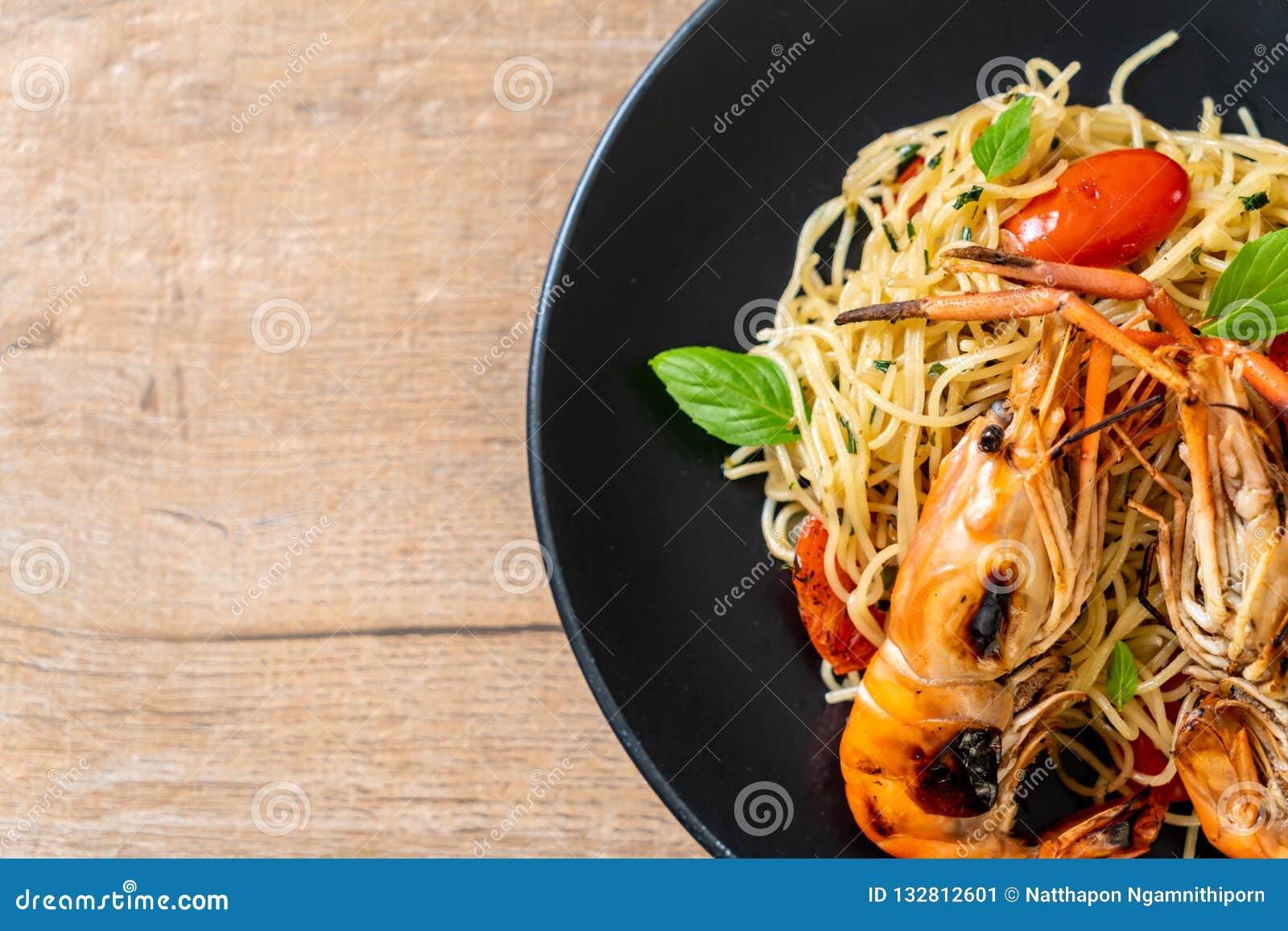 Spaghetti faits sauter à feu vif avec les crevettes et les tomates grillées