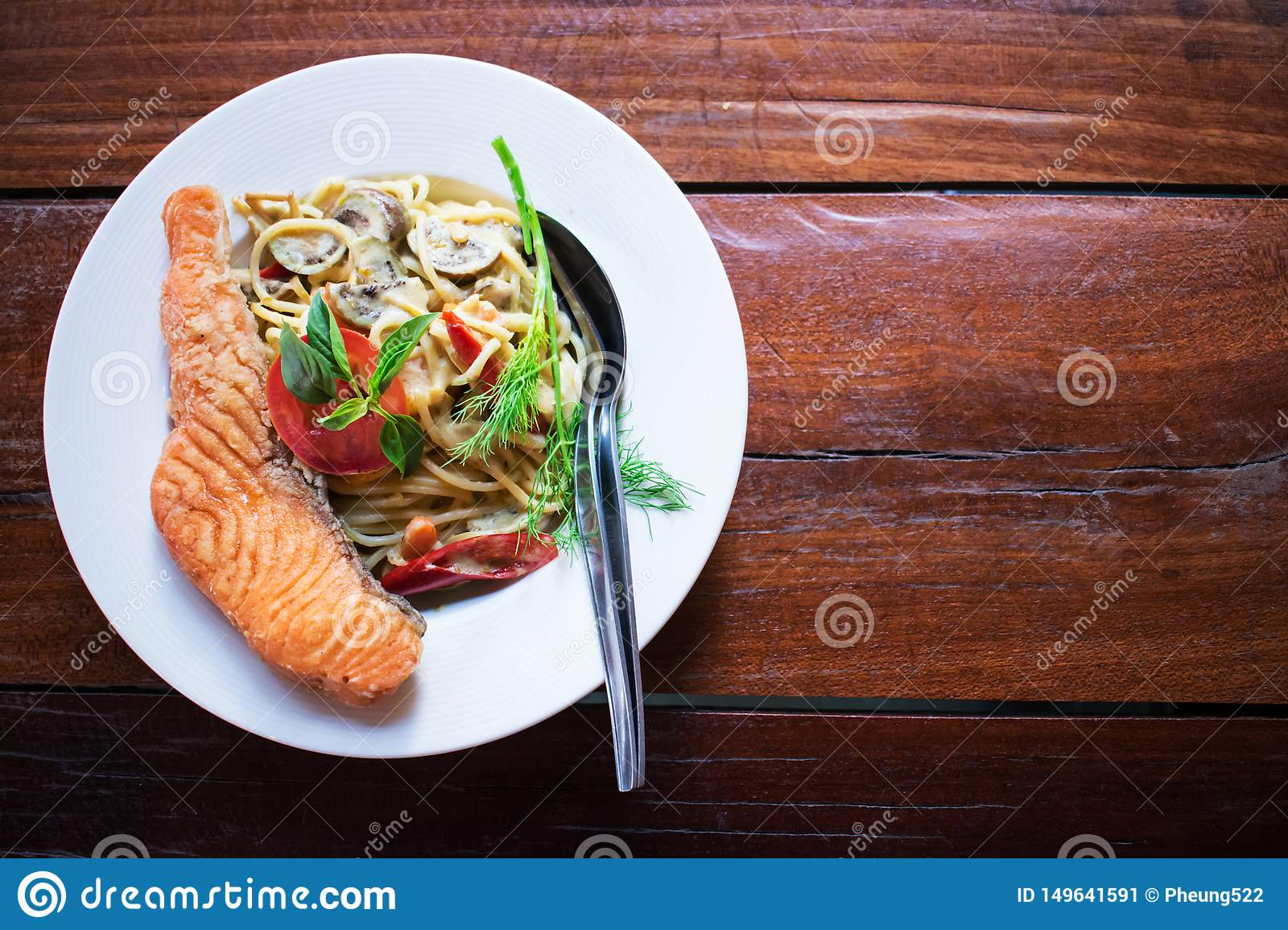 Spaghetti with green curry And a large salmon in a white dish placed on an old wooden table. Thai food