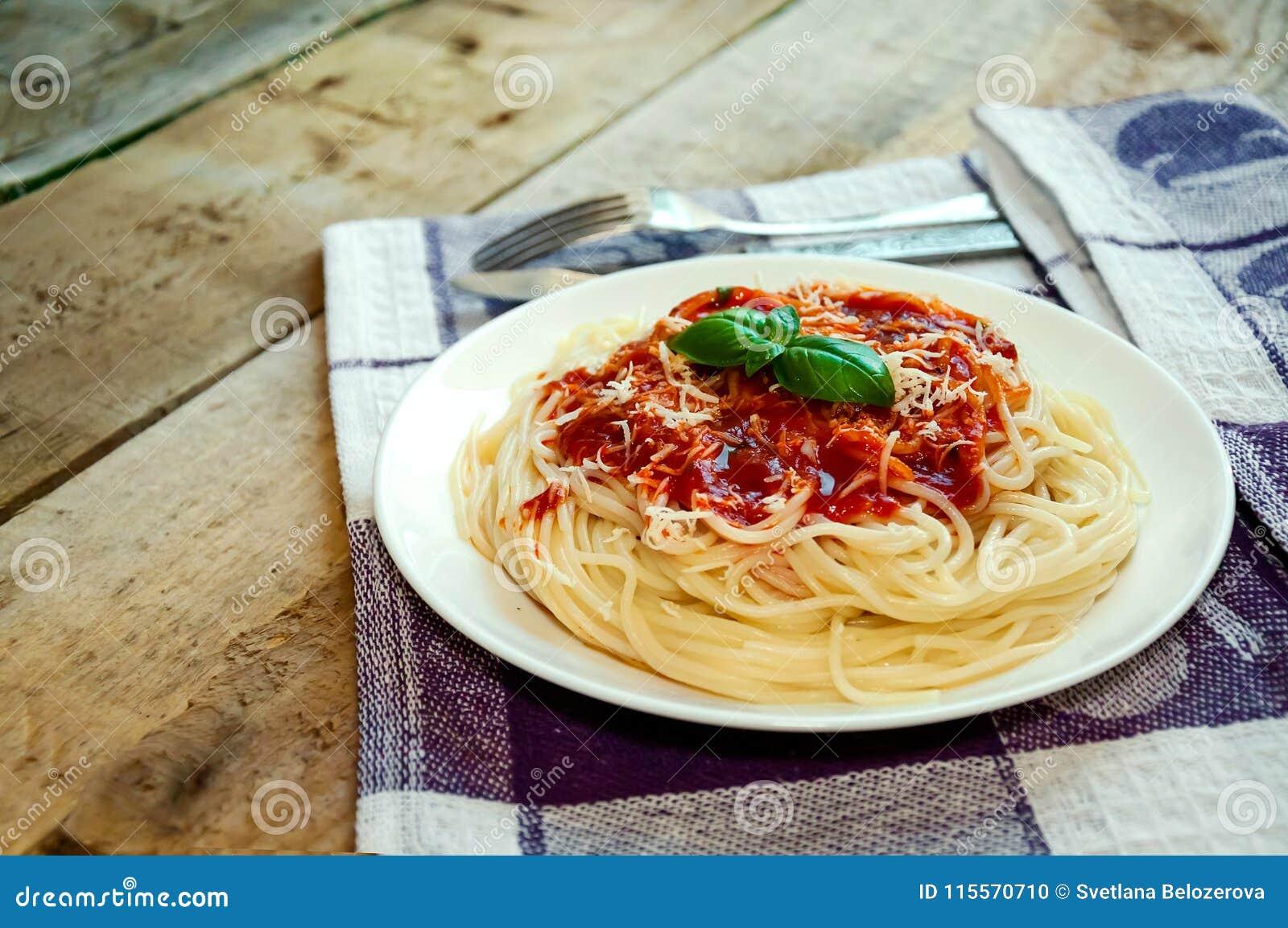 Spaghetti makaron z Pomidorowym kumberlandem, serem i basilem na Drewnianym stole, karmowy włoski tradycyjny