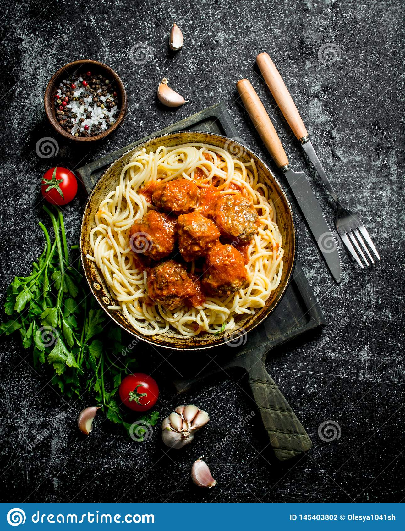 Spaghetti and meat balls in pan with spices, herbs and tomatoes