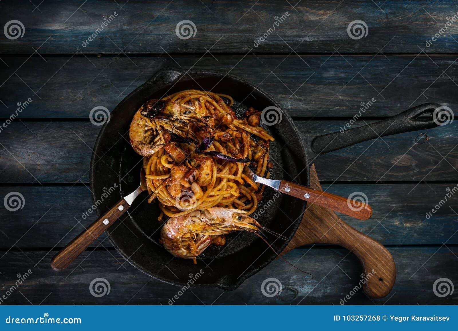 Spaghetti Pasta con frutti di mare su una padella calda con un cucchiaio e la forcella su un fondo di legno colorato Vista superi