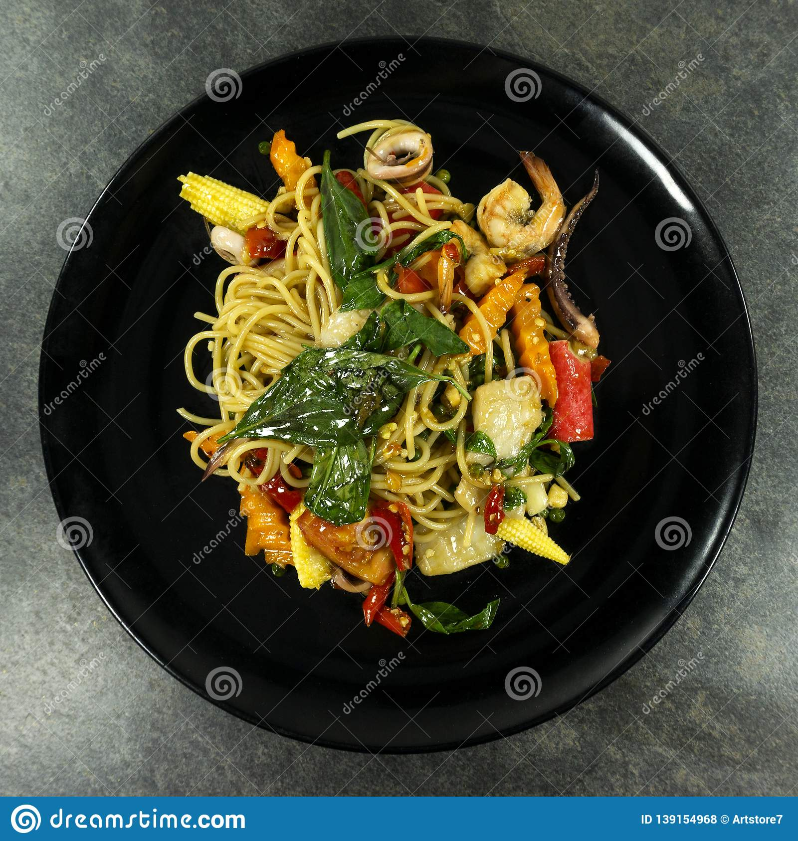 Spaghetti spicy seafood on stone floor table.
