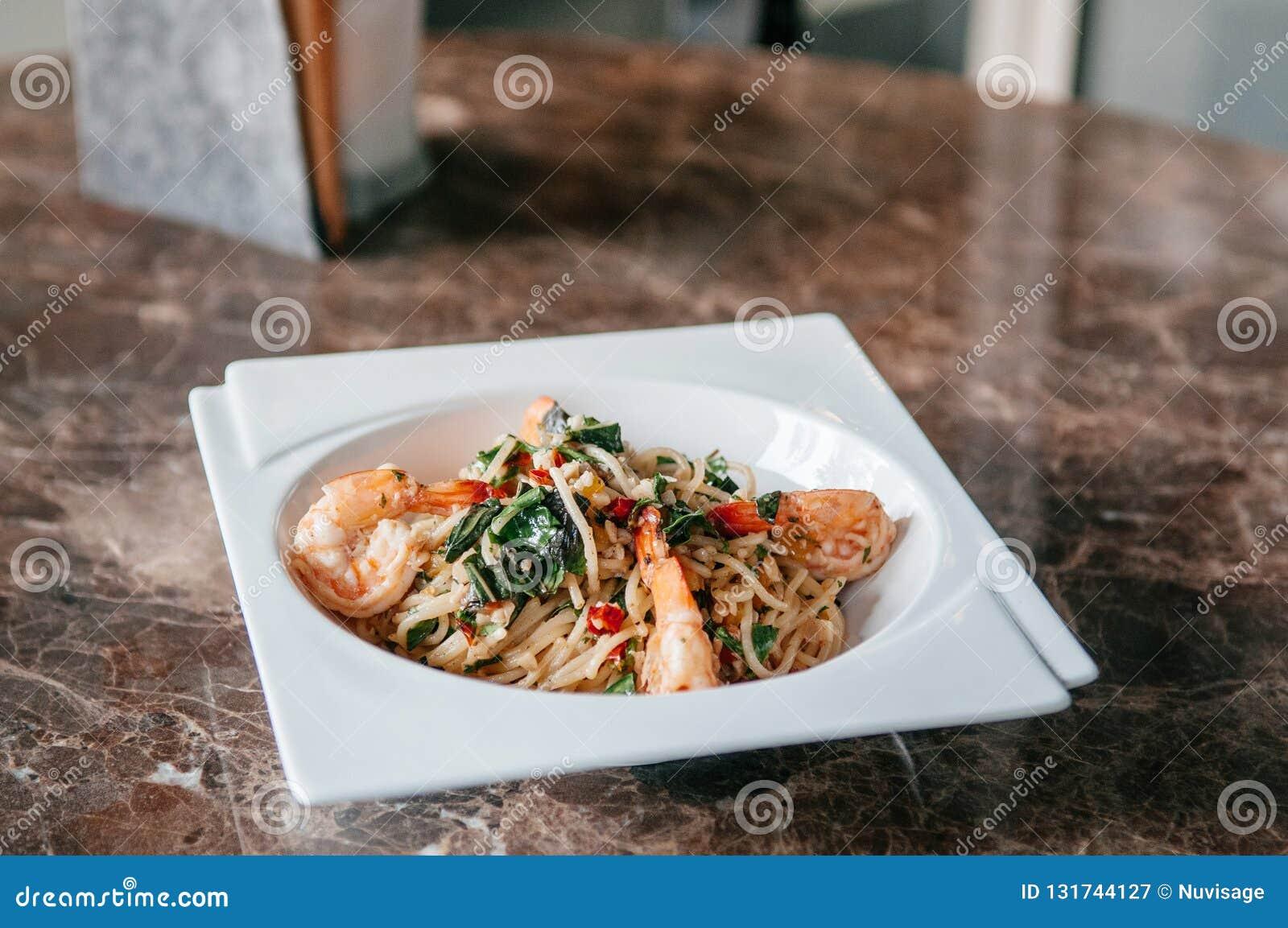 Spaghetti van het Stootkussenkapraw van fusiedeegwaren de kruidige Thaise met knoflook, rode Spaanse pepers, garnalen en heilig b