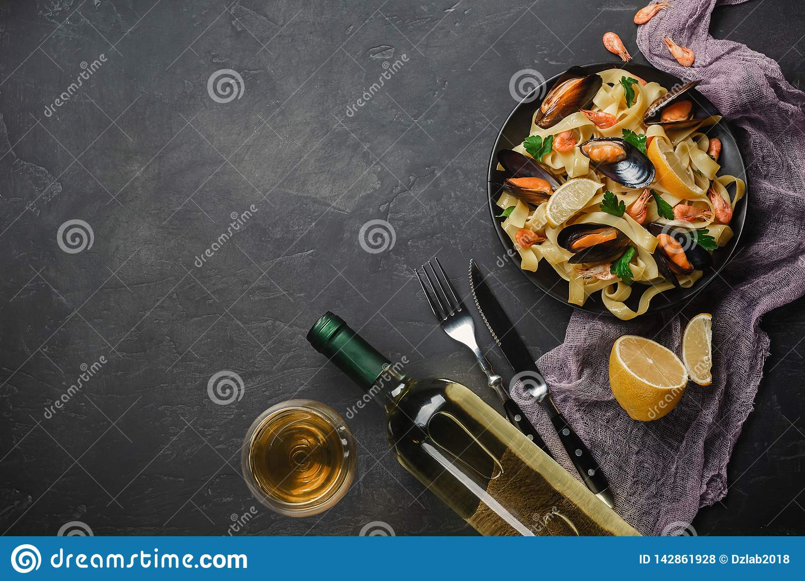 Spaghetti vongole, Italian seafood pasta with clams and mussels, in plate with herbs and glass of white wine on rustic stone