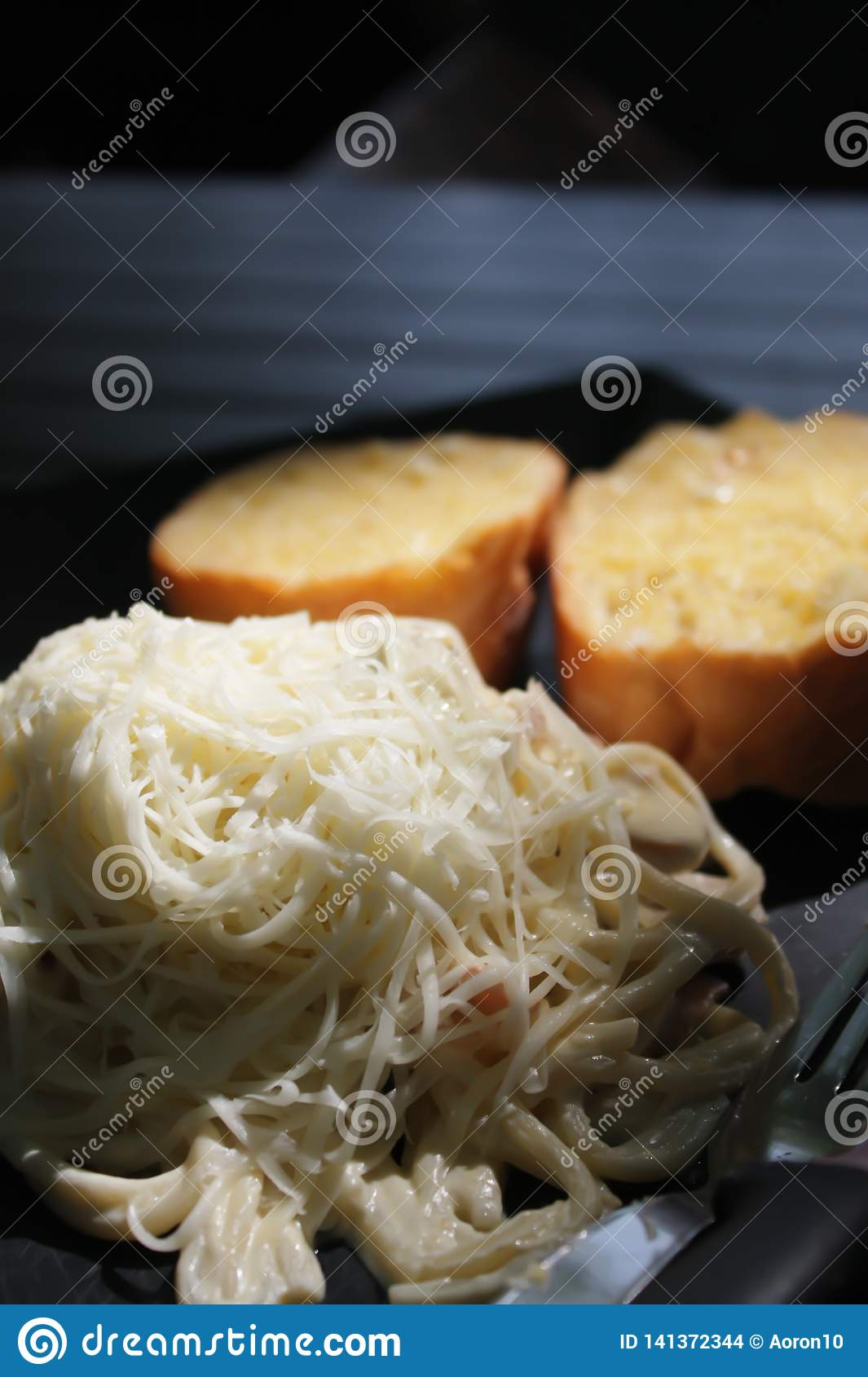 Spaghetti with white sauce, ham and mushrooms topped with cheese and garlic bread served on a black plate.