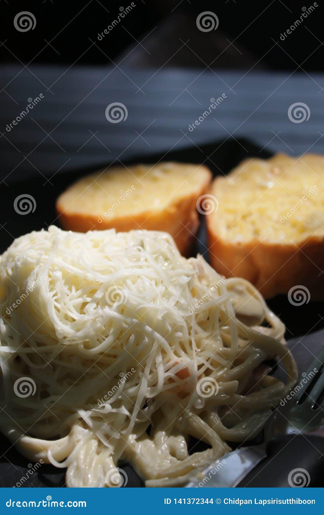 Spaghetti z białym kumberlandem, baleronem i pieczarkami nakrywającymi z, serem i czosnku chlebem słuzyć na czarnym talerzu