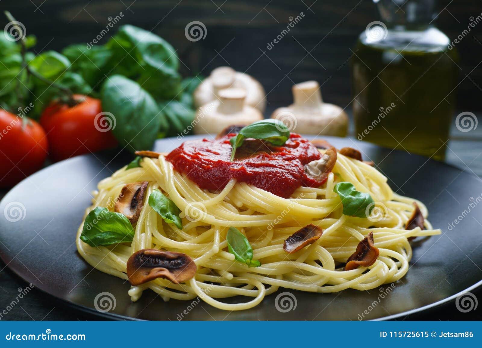 Spaghettideegwaren met tomatensaus, geroosterd champignons en basilicum
