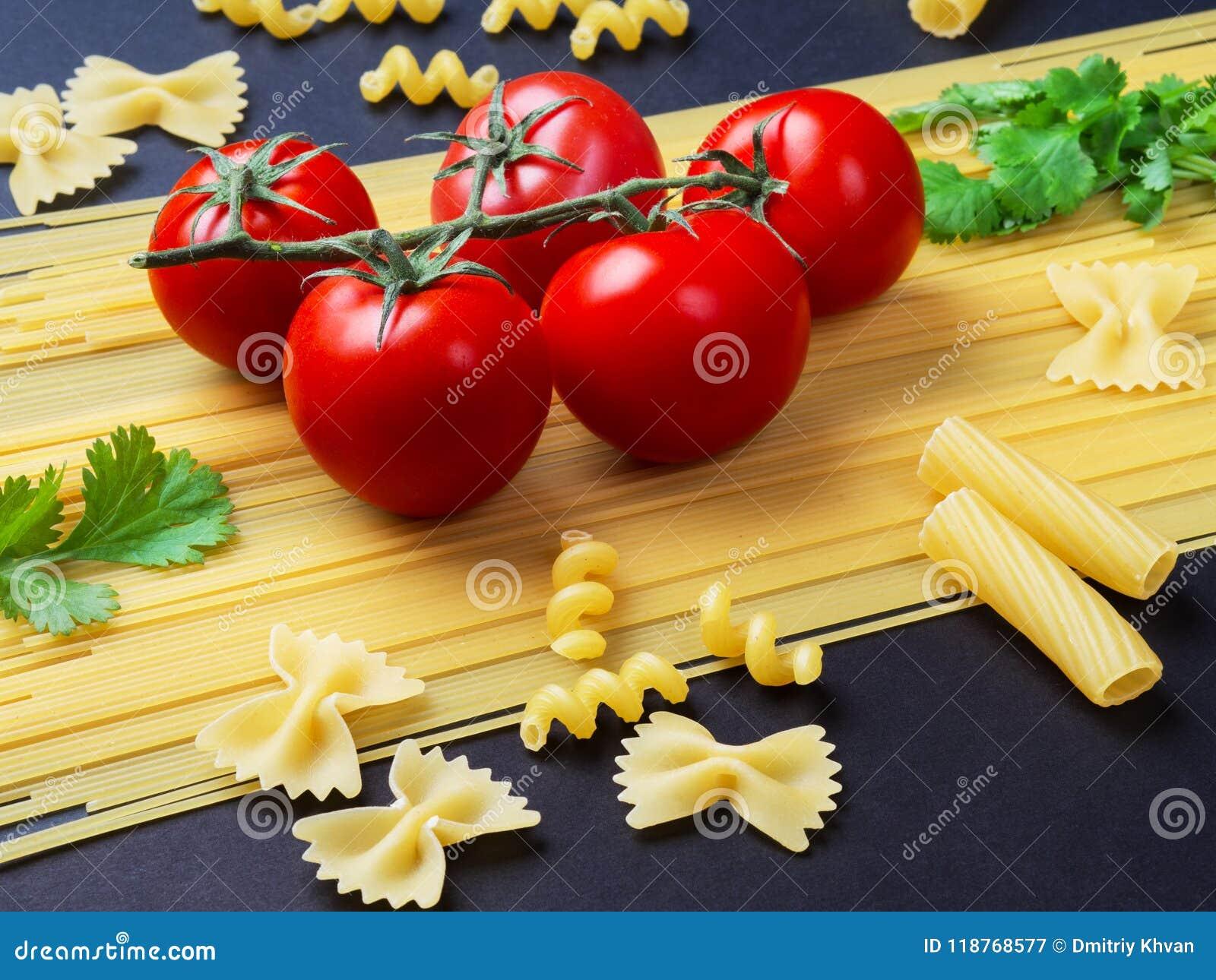 Spaghettis, Tomaten auf einer Niederlassung und Petersilie auf einer Niederlassung auf einem bla