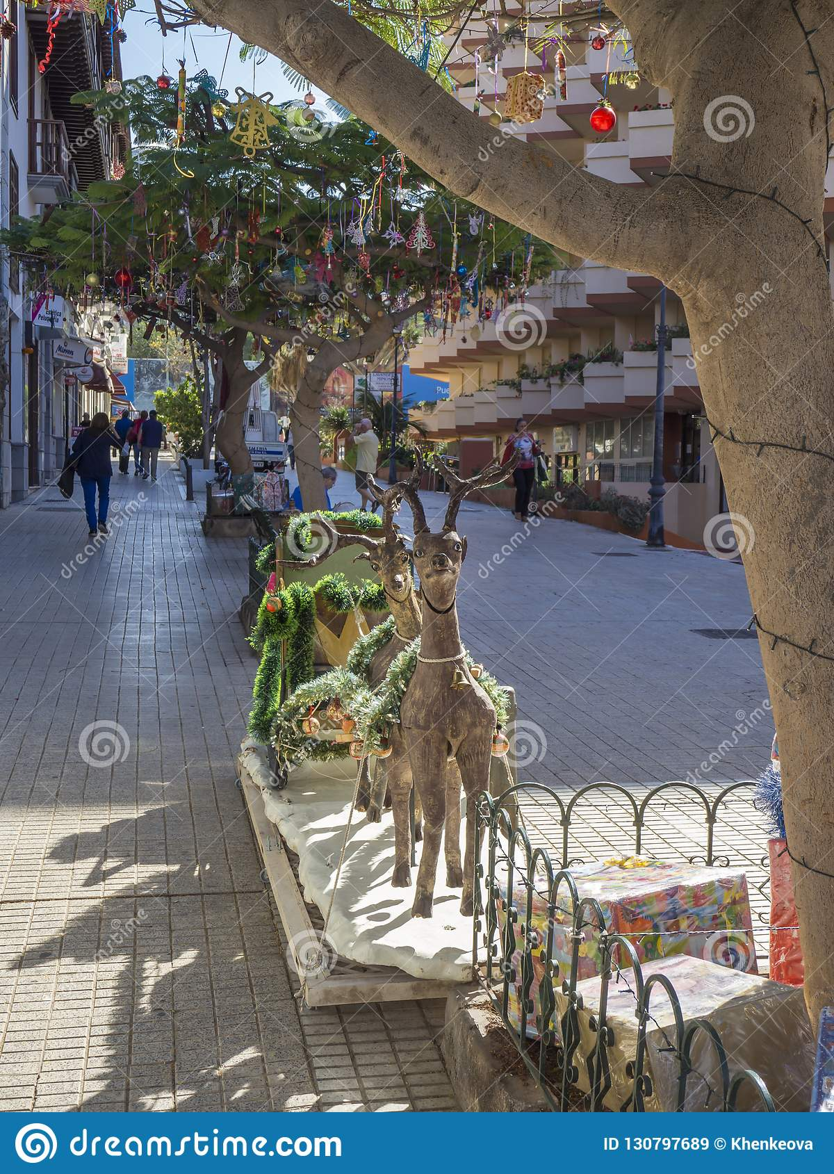 Spain, Canary islands, Tenerife, Puerto de la cruz, December 23, 2017: Street with tropical palm trees decorated with