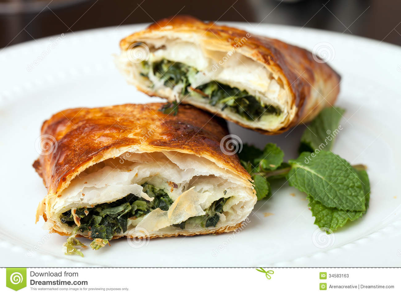Greek spanakopita or spinach pie on a white plate. Shallow depth of ...
