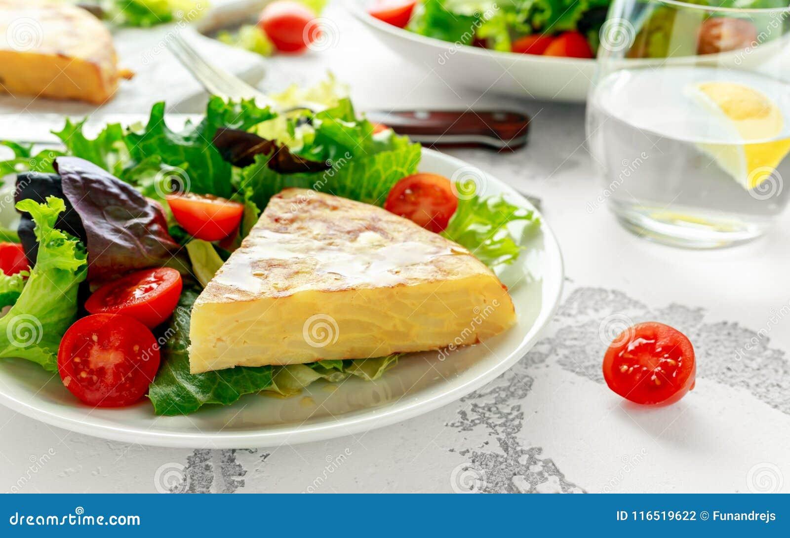 Spanische Tortilla, Omelett mit Kartoffel, Zwiebel, Gemüse, Tomaten, Oliven und Kräuter in einer weißen Platte Frühstück