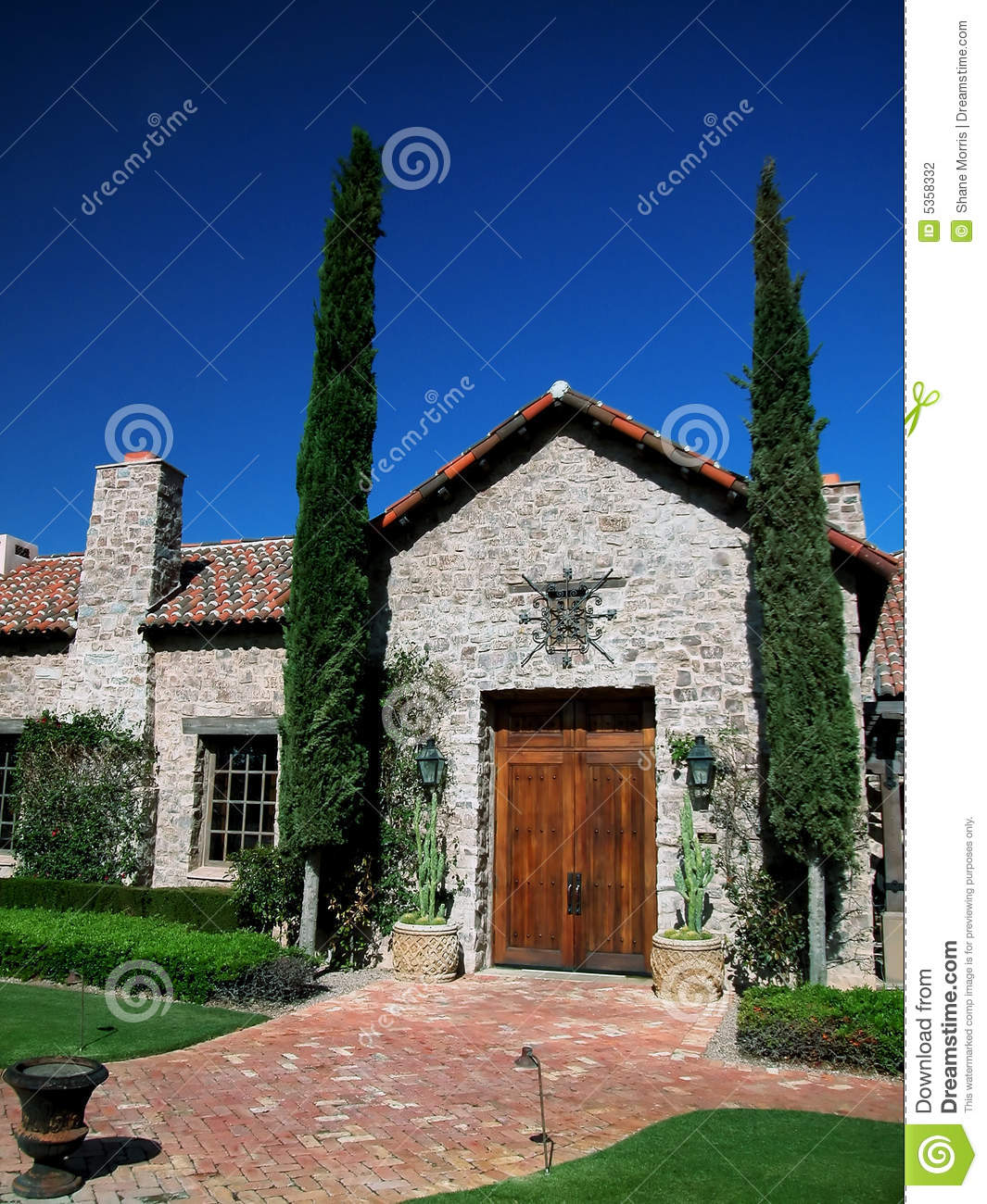 Tuscan House Style With Front Walkway And Italian Cypress: Spanish Styled Villa Entrance Stock Photo