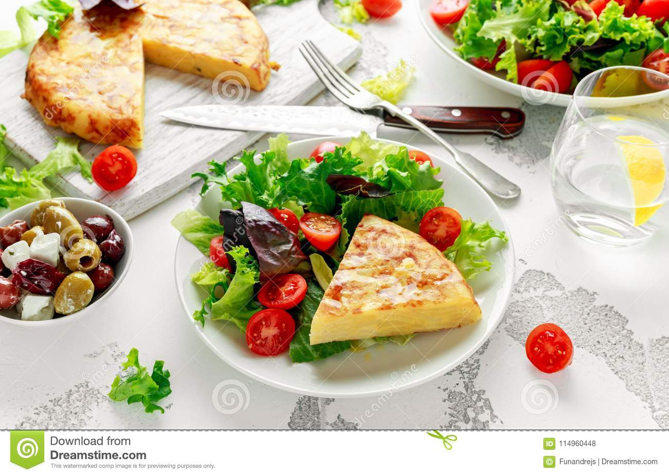 Spanish tortilla, omelette with potato, onion, vegetables, tomatoes, olives and herbs in a white plate. breakfast