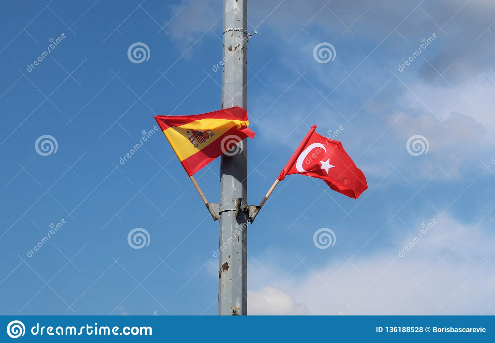 Spanish and Turkish flags in the flagpole on the street lantern with the blue sky in the background