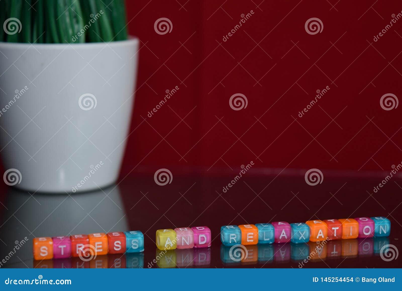 Spanning en ontspanningstekst bij kleurrijk houten blok op rode achtergrond Bureaubureau en onderwijsconcept