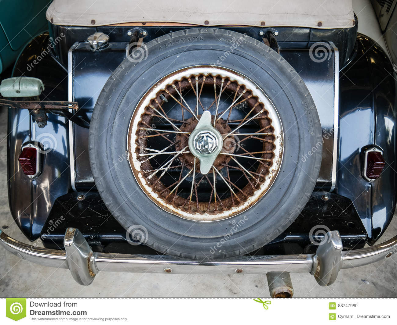 Spare spoke wheel on back trunk of old mythic english car, retro and vintage background