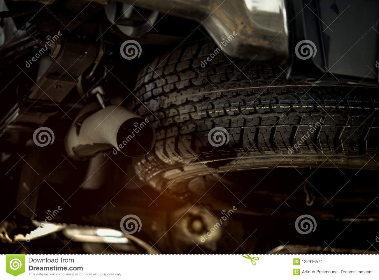 Spare tire under the car near exhaust pipe. Spare wheel. Rubber product. Car check up before travel concept