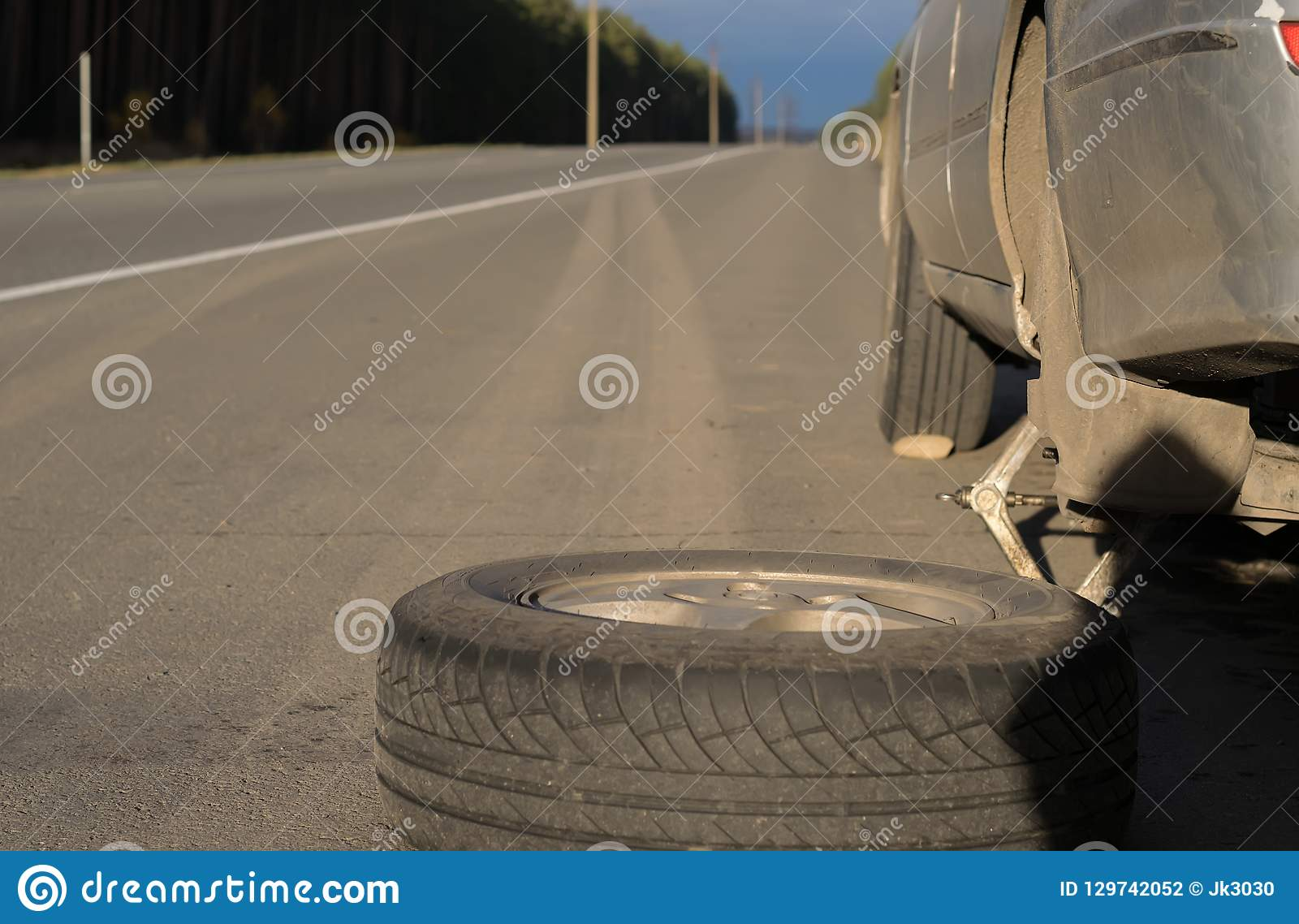 Spare wheel lying near the car. The car is mounted on the Jack