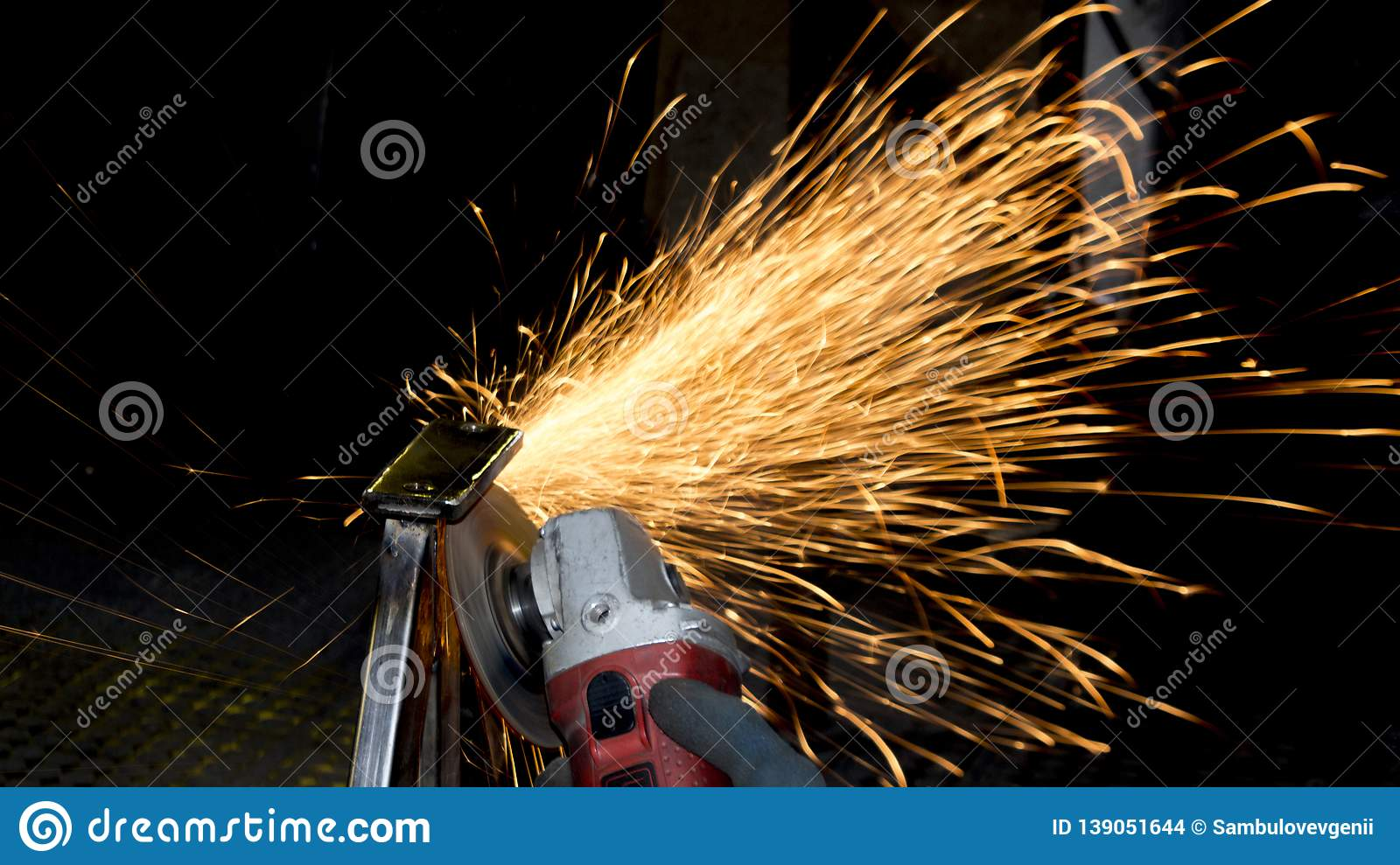 Spark on dark background. Processing of metal products and metal structures at the factory, factory, enterprise and organization.