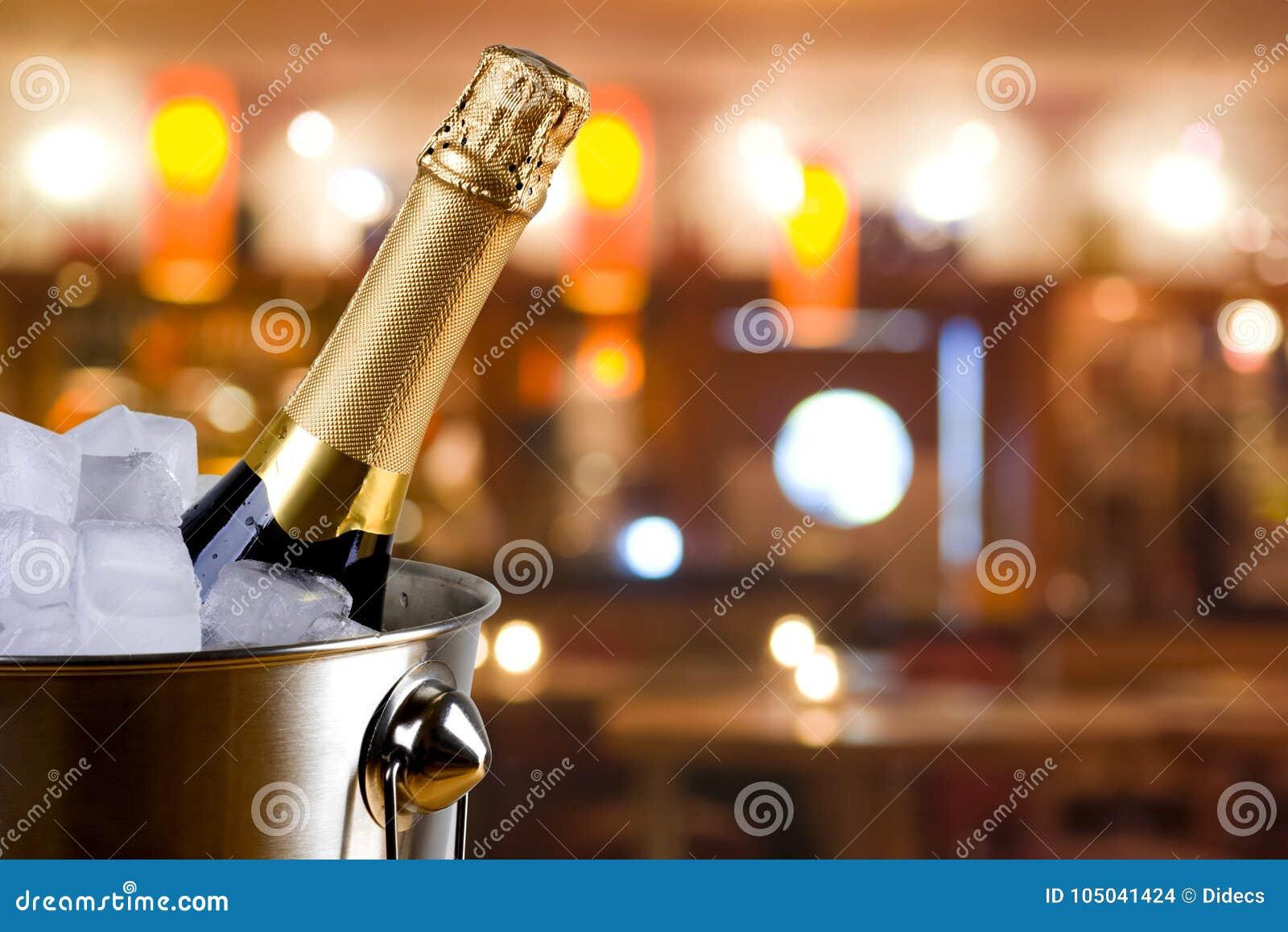 Sparkling wine bottle in ice bucket on blurred restaurant background