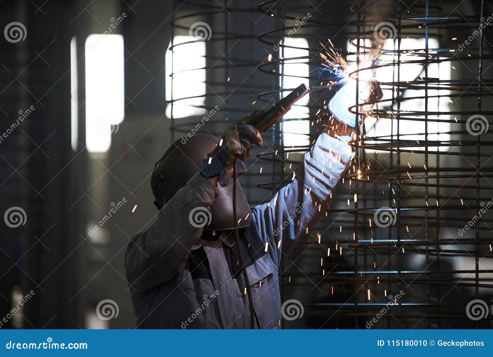 Spawacza mężczyzna spawki przy fabryką