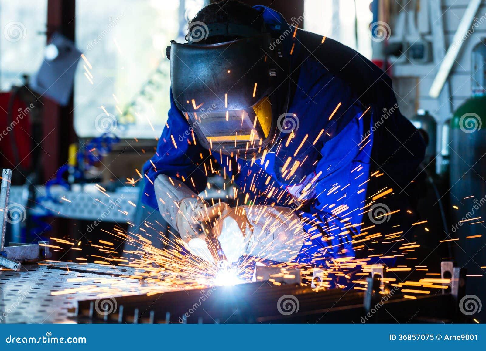 Spawacza spawalniczy metal w warsztacie z iskrami