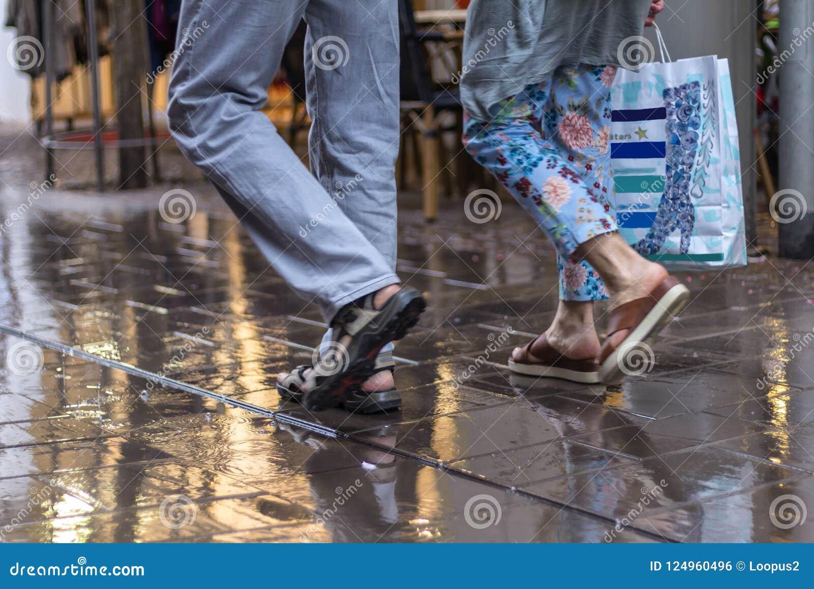 Spaziergang auf und ab die Straße durch den Regen