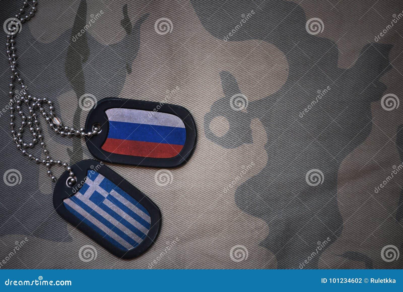 Spazio in bianco dell esercito, medaglietta per cani con la bandiera della Russia e la Grecia sui precedenti cachi di struttura