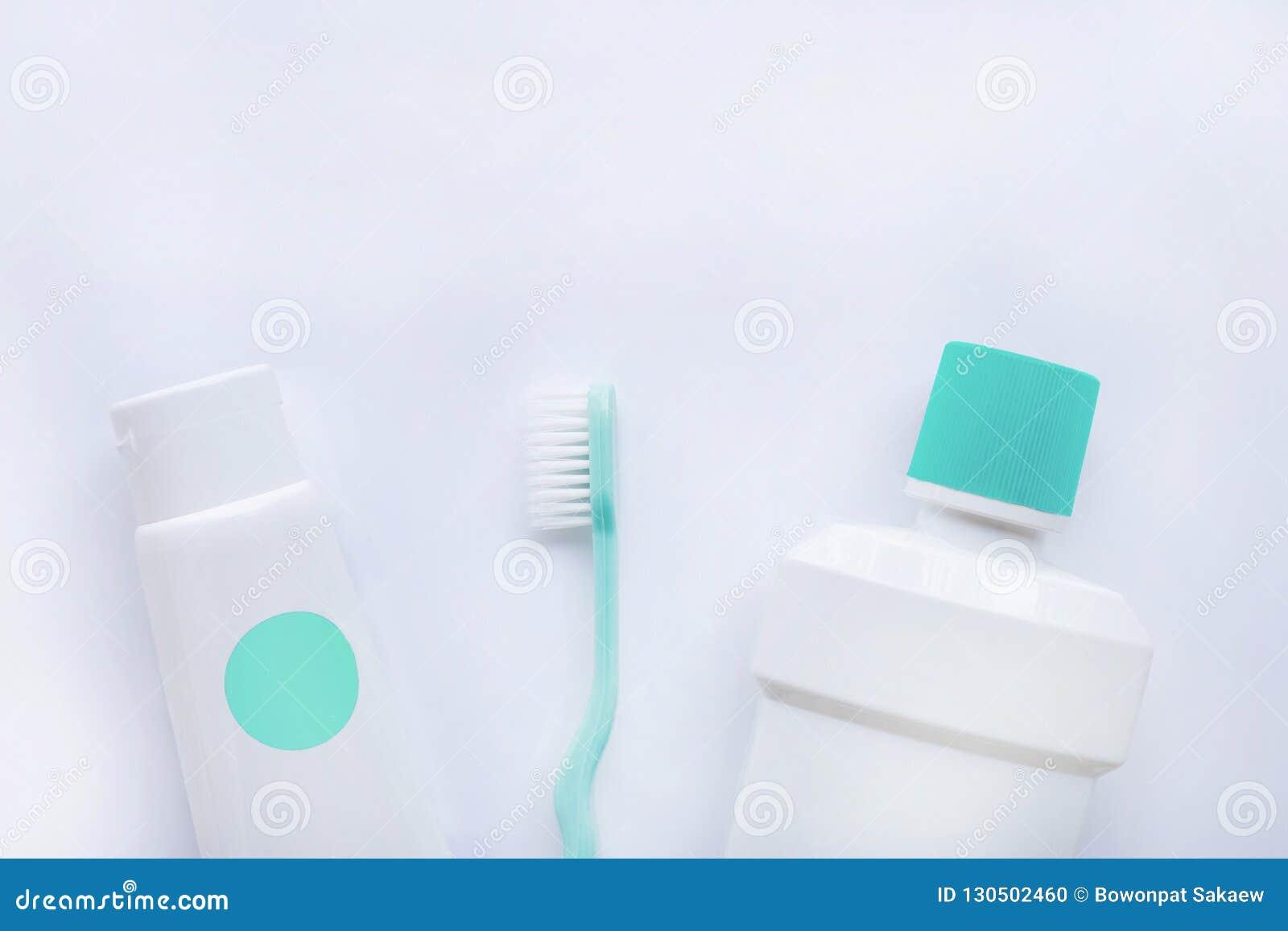 Spazzolino da denti e dentifricio in pasta con la bottiglia di colluttorio sul BAC bianco