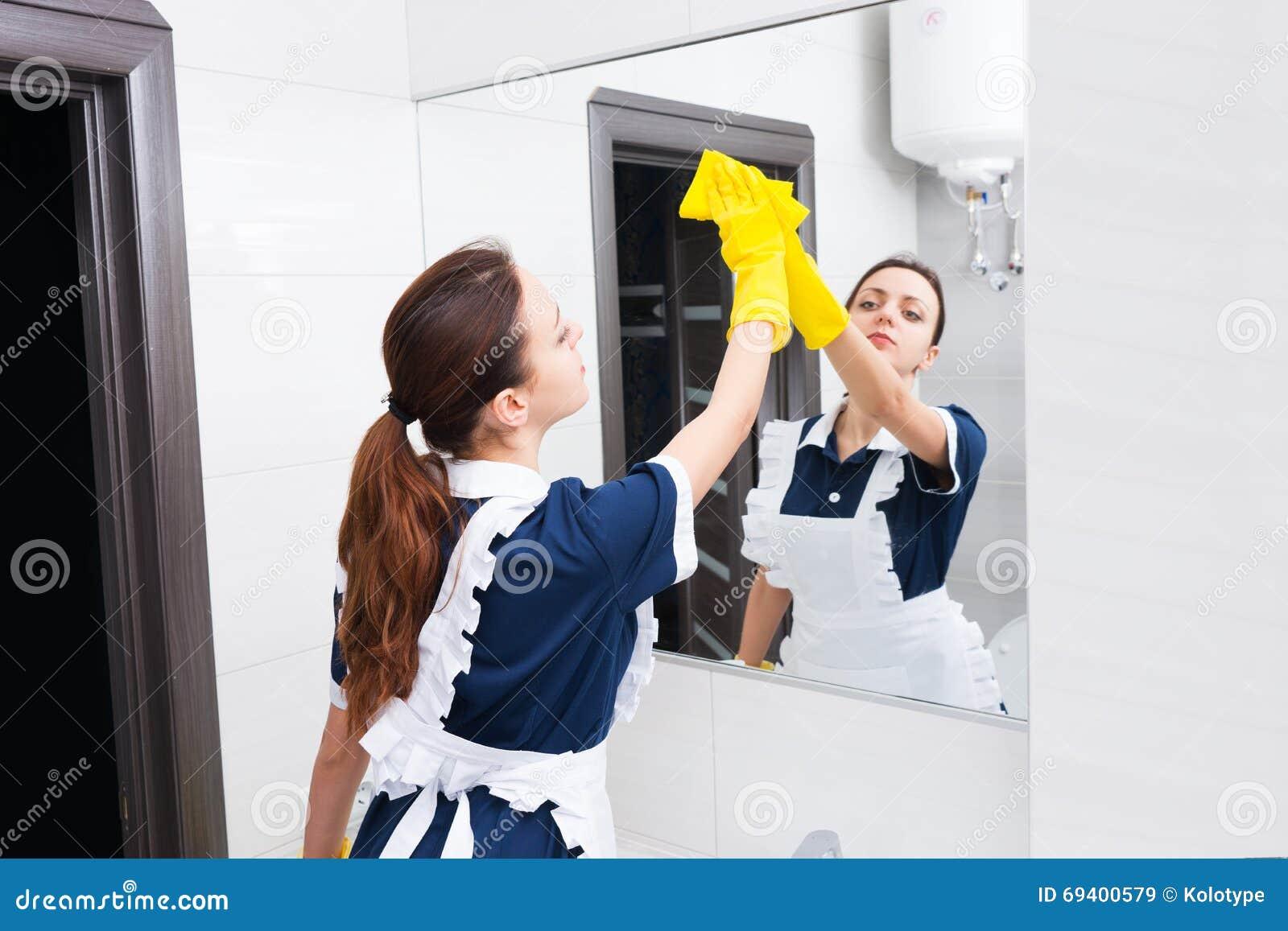 Specchio del bagno di pulizia della domestica con la for Pulizia bagno