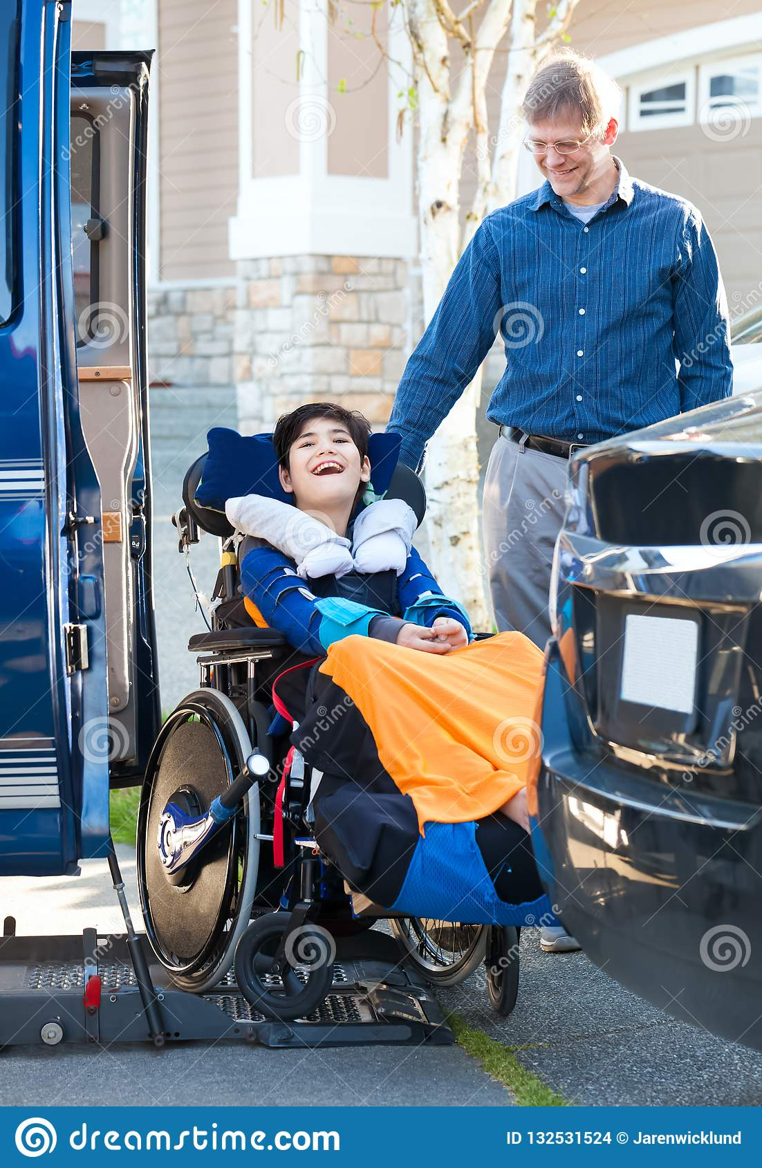 Special needs boy in wheelchair on vehicle handicap lift
