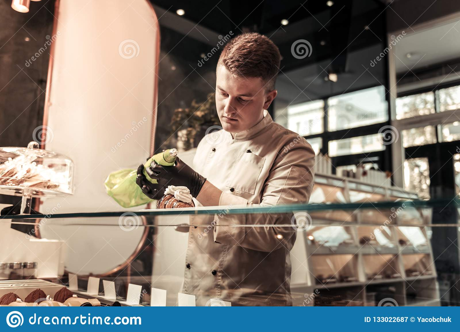 Serious smart confectioner holding a pastry bag