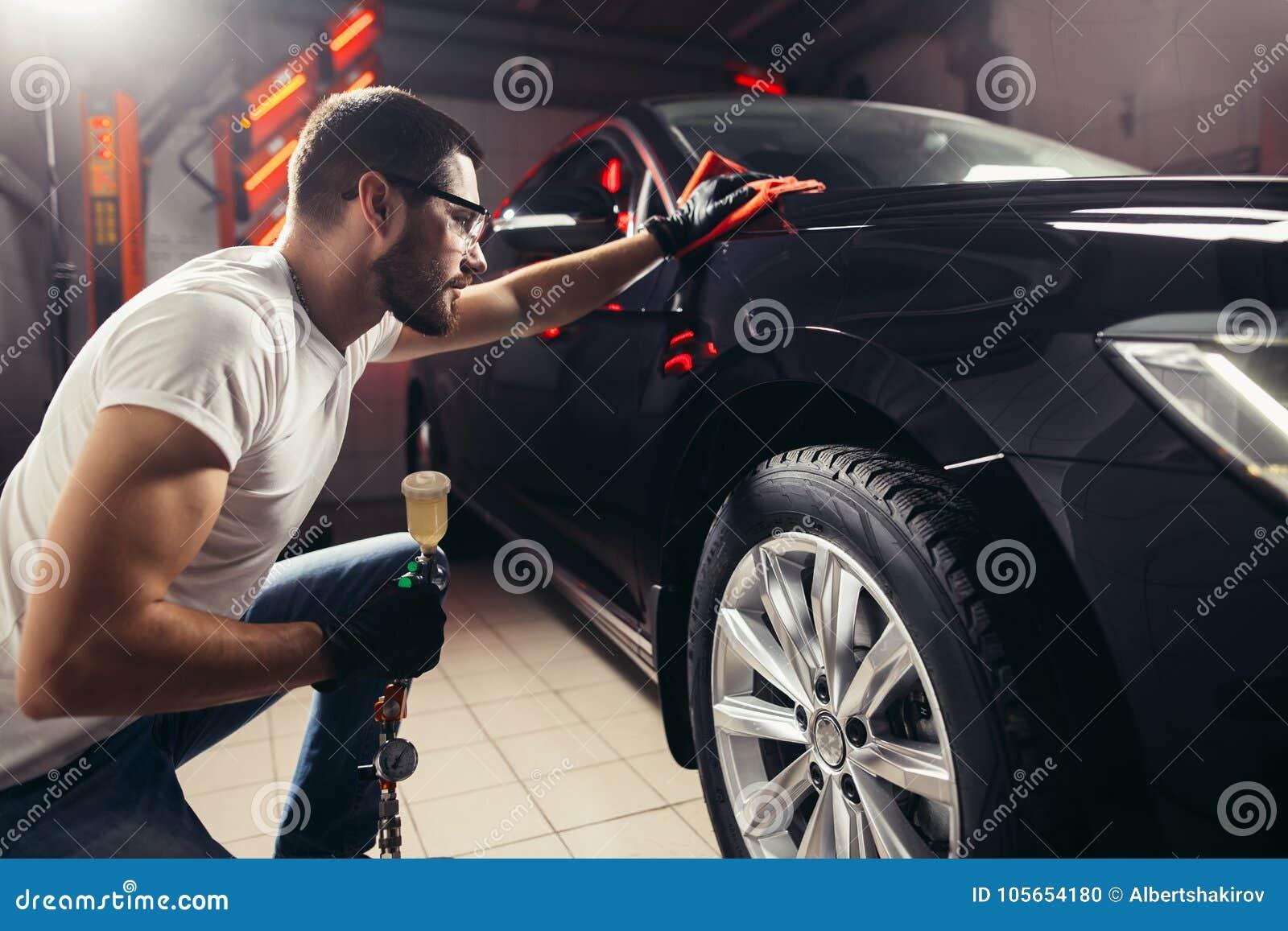Specificera för bil - mannen rymmer microfiberen i hand och polerar bilen