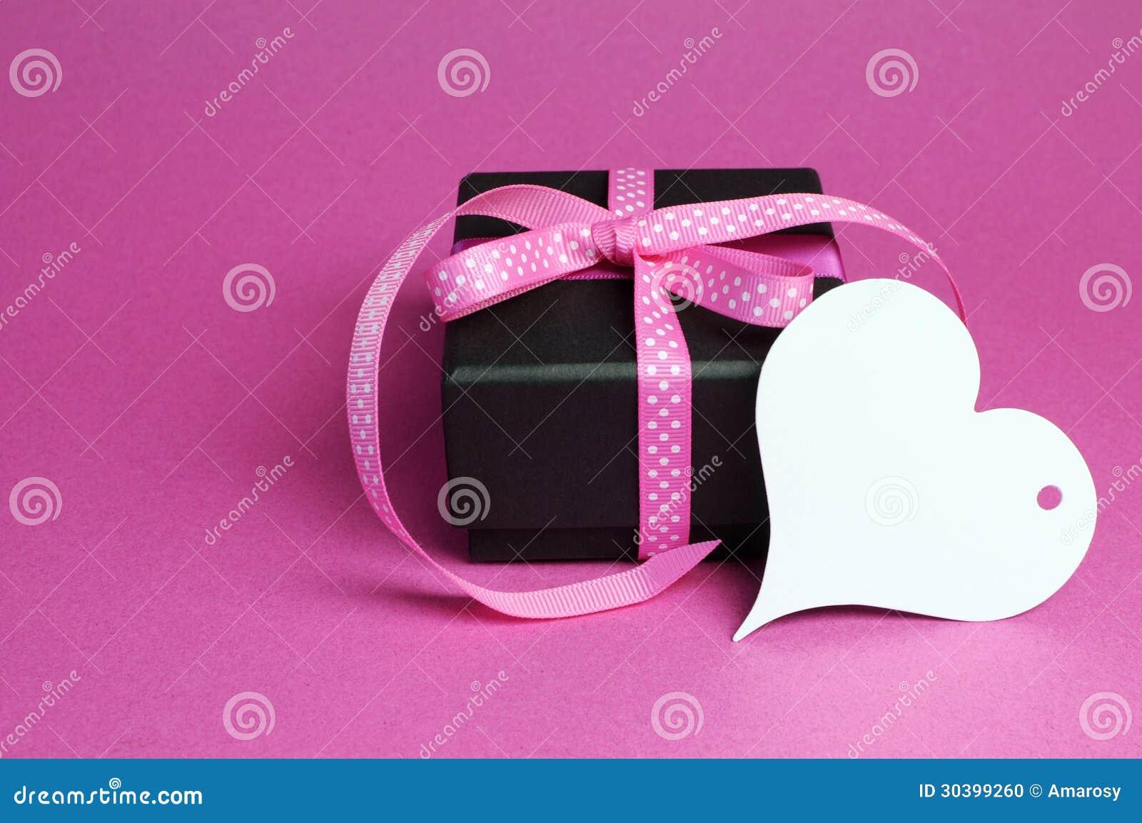 Specjalny mały czarnego pudełka teraźniejszości prezent z różowym polki kropki faborkiem i białą kierową kształta prezenta etykiet