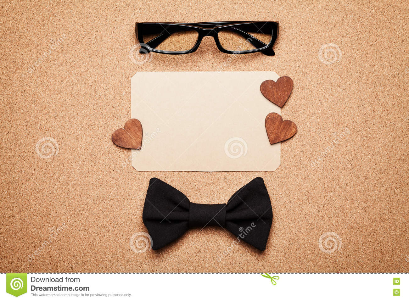 Spectacles, bowtie and empty paper blank in Happy Fathers Day, cork board background, top view, flat lay